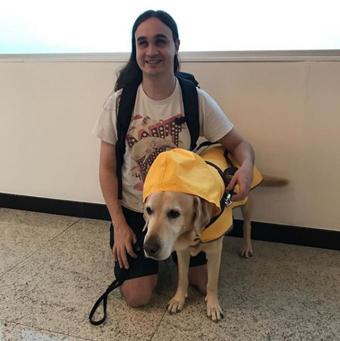 Um rapaz cego, com cabelos longos, está ajoelhado abraçando o labrador caramelo Tmmy, que veste uma capa de chuva amarela